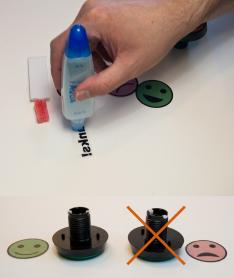 Top: Hand applying glue to the back of stickers. Bottom: Two buttons and two stickers. The left button is paired with a green smiling face sticker aligned parallel to the guide pegs on the underside of the button. The right button has an 'X' through it, showing that the frowning sticker was not properly aligned with the guide pegs.