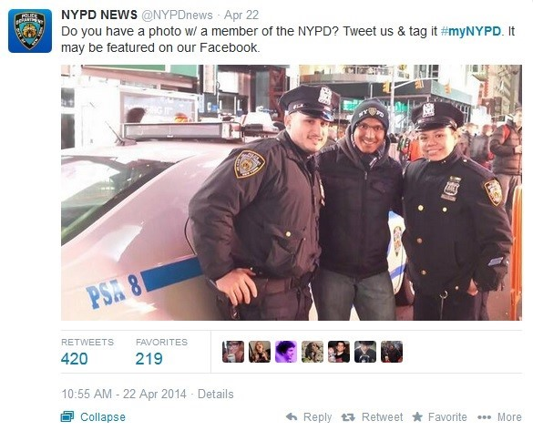 Man smiling and posing with two NYPD officers.